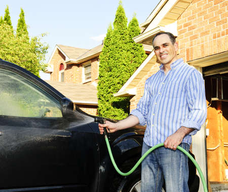 car wash: Man washing his car on the driveway Stock Photo