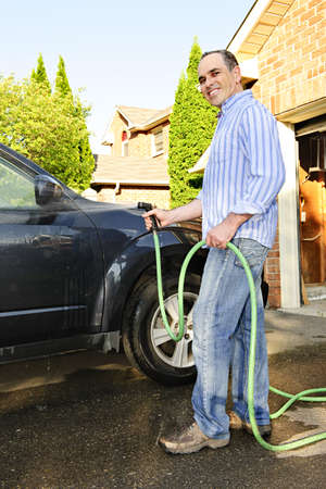 Man washing his car on the driveway photo