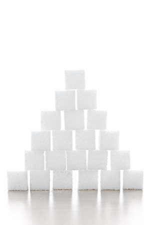 stacked up: Pyramid of white sugar cubes stacked up on white background Stock Photo