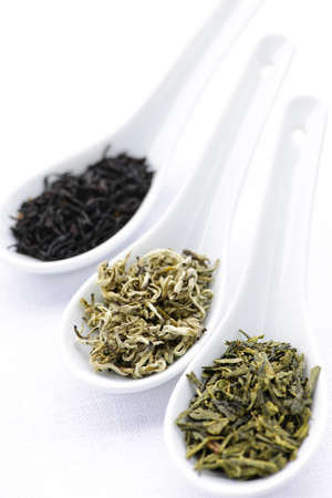 Black, white and green dry tea leaves in spoons Imagens