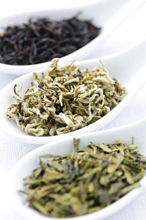 Black, white and green dry tea leaves in spoons photo