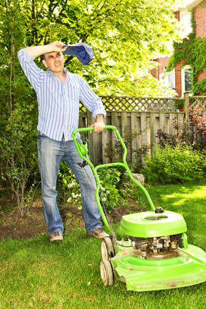 gras maaien: Man die het nemen van een pauze tijdens het gazon maaien op een warme zomer dag