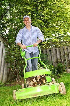 gras maaien: Man met gazon maaier in aangelegde achtertuin