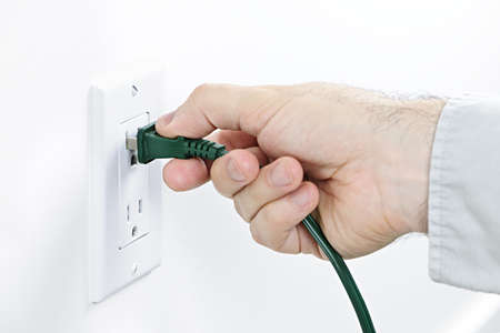 Hand inserting green electrical plug into outlet photo