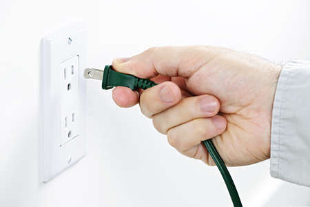 plugging: Hand inserting green electrical plug into outlet Stock Photo