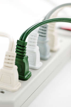 Many plugs plugged into electric power bar photo
