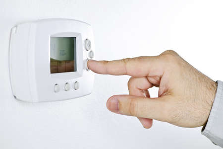 Closeup of hand pressing button on digital thermostat Stock Photo