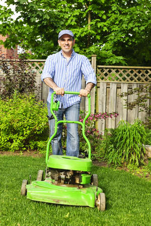 lawn mower: Man with lawn mower in landscaped backyard Stock Photo