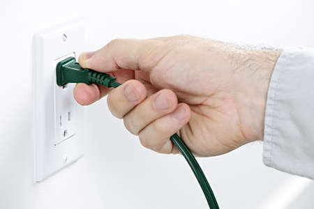 Hand pulling green electrical plug from outlet photo