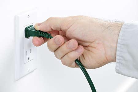 toma corriente: Mano tirando de enchufe el�ctrico verde de salida