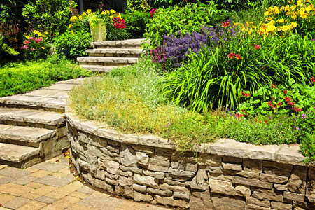 Natural stone landscaping in home garden with stairs and retaining walls photo