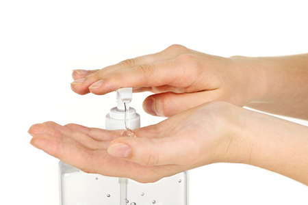 Female hands using hand sanitizer gel pump dispenser photo