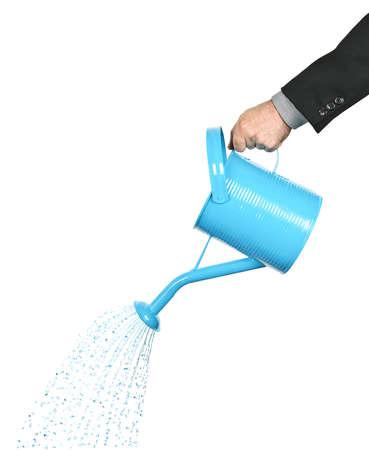 Mano di un imprenditore versando acqua da annaffiatoio