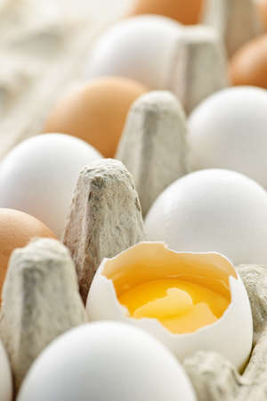 White and brown eggs in carton with broken egg photo