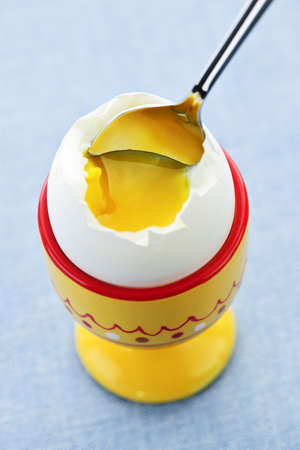 Closeup of soft boiled egg in cup with spoon Stockfoto