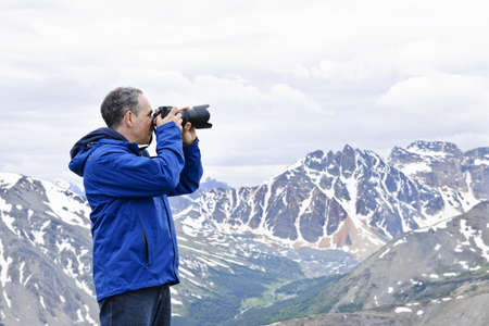 Male photographer taking pictures in Canadian Rocky Mountains in Jasper National Park Stock Photo - 7745796