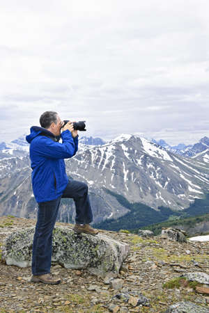 Male photographer taking pictures in Canadian Rocky Mountains in Jasper National Park Stock Photo - 7745805