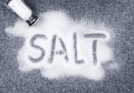 shaker: Salt written on counter in spilled salts from shaker Stock Photo