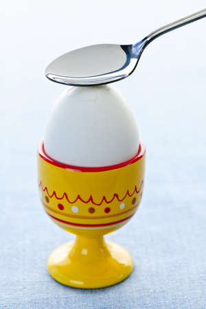 Breaking open a soft boiled egg in cup with spoon