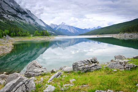 reflecting: Mountains reflecting in Medicine Lake in Jasper National Park, Canada Stock Photo