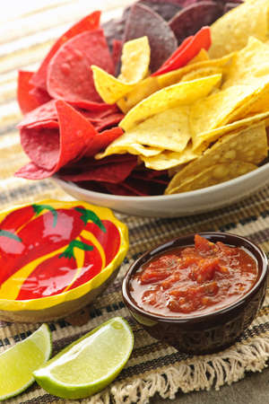 chips and salsa: Bowl of salsa with colorful tortilla chips and lime Stock Photo