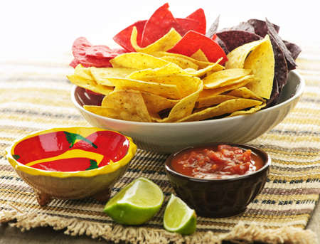 dipping: Bowl of salsa with colorful tortilla chips and lime Stock Photo
