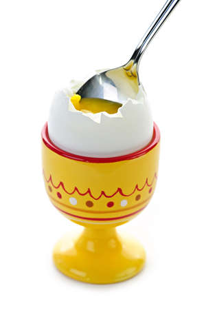 Closeup of soft boiled egg in cup with spoon on white background photo