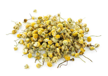Stapel van medicinale gele kamille kruid toppen op witte achtergrond Stockfoto