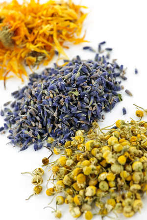botanical remedy: Piles of dried medicinal herbs camomile, lavender, calendula on white background Stock Photo