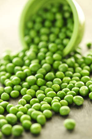 legumes: Closeup on spilling bowl of fresh green green peas Stock Photo
