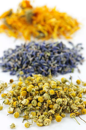 alternative medicine: Piles of dried medicinal herbs camomile, lavender, calendula on white background Stock Photo