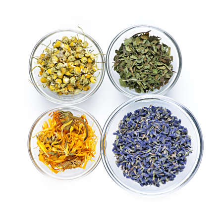 dried herb: Bowls of dry medicinal herbs on white background from above Stock Photo