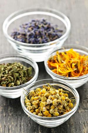 Assortimento di erbe medicinali secco in ciotole di vetro  Archivio Fotografico - 7881280