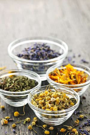 Assortment of dry medicinal herbs in glass bowls Banco de Imagens