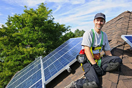 Man installing alternative energy photovoltaic solar panels on roof Stock Photo - 7881290