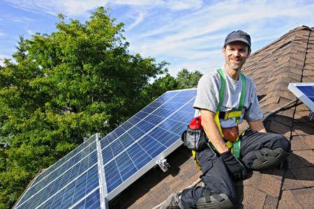 Man installing alternative energy photovoltaic solar panels on roof Stock Photo - 7881290