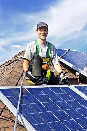 Man installing alternative energy photovoltaic solar panels on roof photo