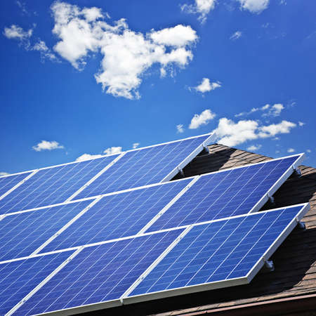 Array of alternative energy photovoltaic solar panels on roof photo