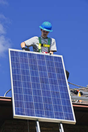 Man installing alternative energy photovoltaic solar panels on roof Stock Photo - 7881454