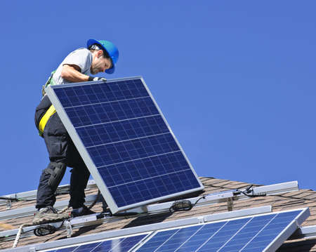 Man installing alternative energy photovoltaic solar panels on roof Stock Photo - 7881452