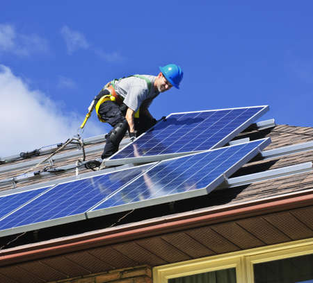 energy work: Man installing alternative energy photovoltaic solar panels on roof