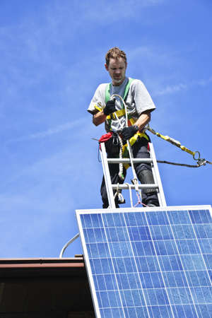 panel: Man installing alternative energy photovoltaic solar panels on roof
