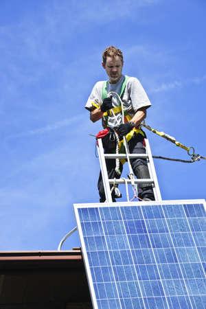Man installing alternative energy photovoltaic solar panels on roof Stock Photo - 7881268