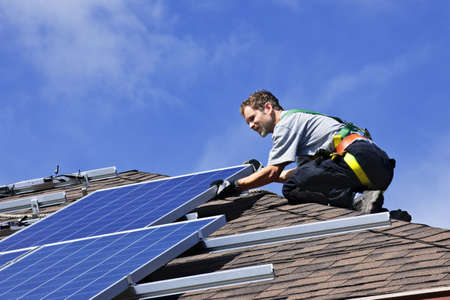 photovoltaic: Man installing alternative energy photovoltaic solar panels on roof