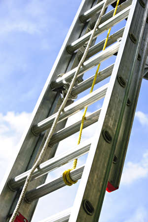 Closeup of construction aluminum extension ladder against blue sky 스톡 콘텐츠