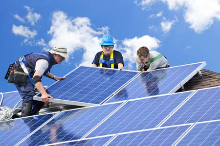Workers installing alternative energy photovoltaic solar panels on roof Stock Photo - 7881276