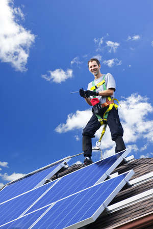 Worker installing alternative energy photovoltaic solar panels on roof photo