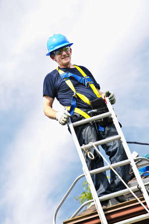 rungs: Construction worker standing on roof near ladder