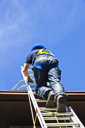 climbing ladder: Construction worker climbing extension ladder to roof