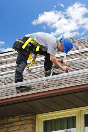 panel: Man installing rails for solar panels on residential house roof